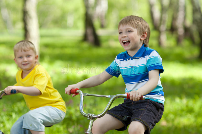 Piccoli bambini che guidano le loro bici immagine stock libera da diritti