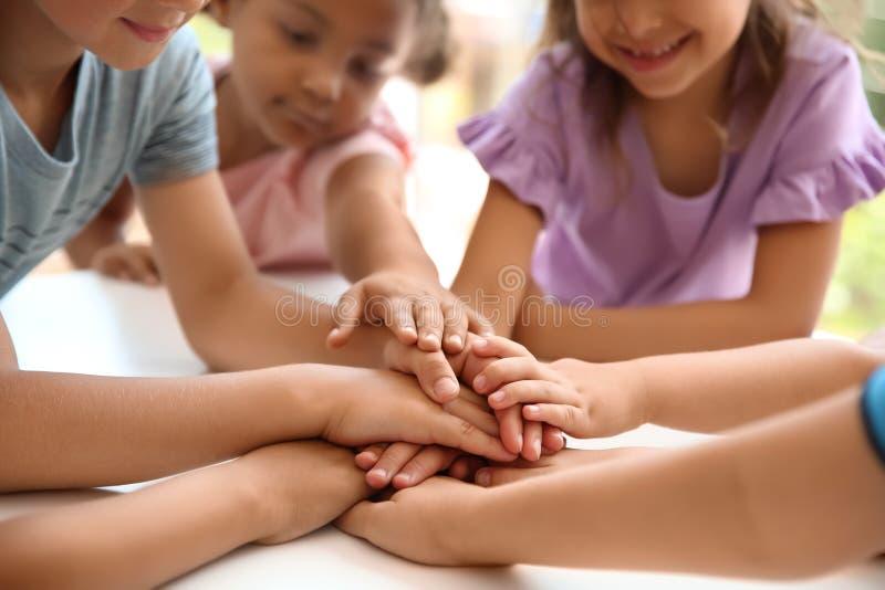 Piccoli bambini che un le loro mani alla tavola fotografia stock libera da diritti
