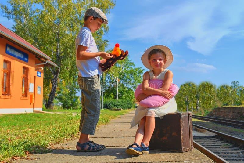 Piccoli bambini - ragazza e ragazzo su una stazione ferroviaria, aspettante il treno con la valigia d'annata Viaggio, festa e chi fotografie stock libere da diritti