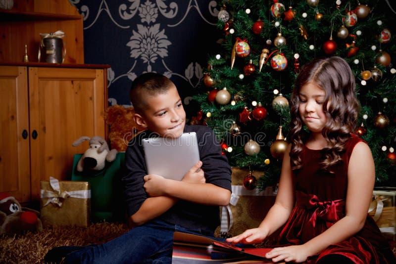 Piccoli bambini svegli che aprono un presente fotografie stock libere da diritti