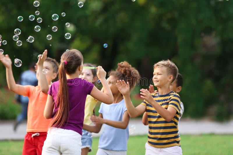 Piccoli bambini svegli che giocano con le bolle di sapone fotografie stock libere da diritti