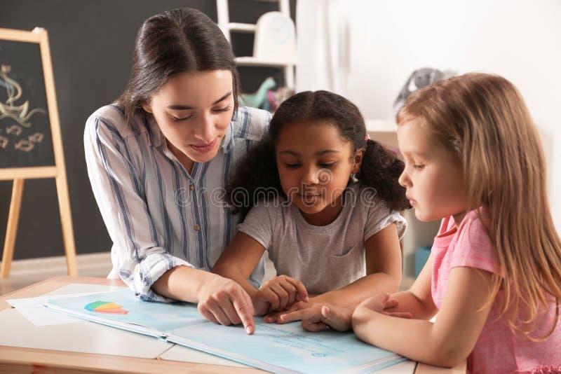 Piccoli bambini svegli con il libro di lettura dell'insegnante della scuola materna alla tavola Attivit? dell'interno immagini stock libere da diritti