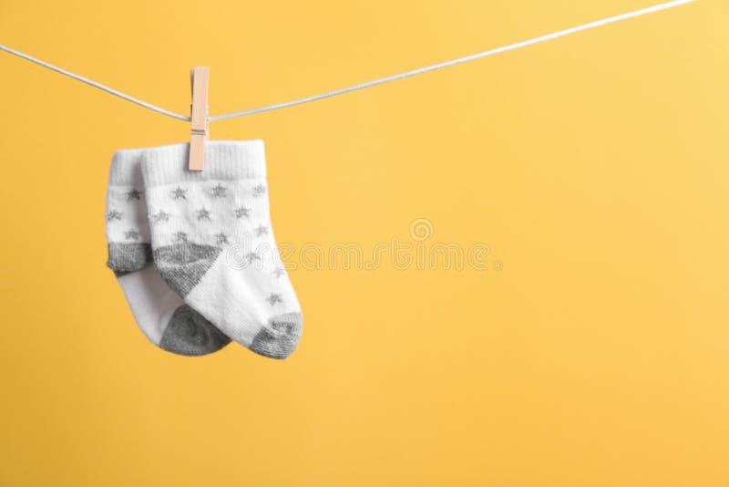 Piccoli calzini che appendono sul lavare linea contro il fondo di colore Accessori del bambino fotografia stock