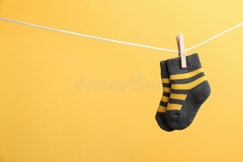 Piccoli calzini che appendono sul lavare linea contro il fondo di colore Accessori del bambino immagini stock libere da diritti
