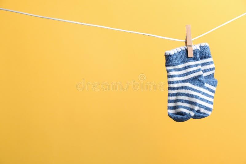 Piccoli calzini che appendono sul lavare linea contro il fondo di colore Accessori del bambino immagini stock