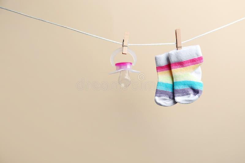 Piccoli calzini e tettarella che appendono sul lavare linea contro il fondo di colore Accessori del bambino immagine stock libera da diritti