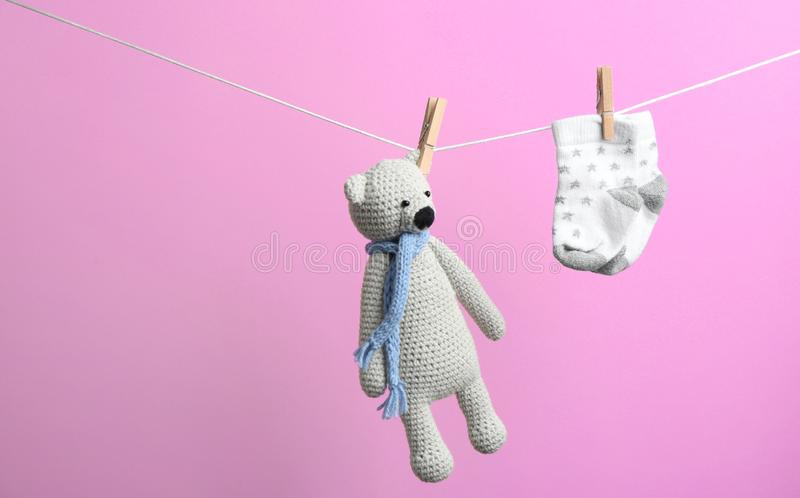 Piccoli calzini ed orso del giocattolo che appende sul lavare linea contro il fondo di colore Accessori del bambino fotografia stock libera da diritti