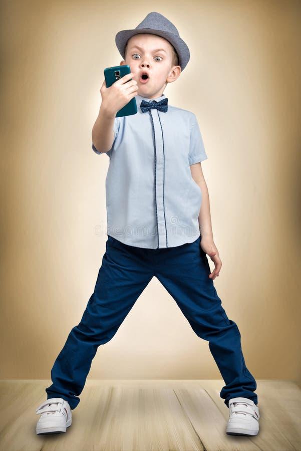 Piccoli colloqui del capo sul suo telefono cellulare Conversazione impressionabile Modo del ` s del bambino immagine stock libera da diritti