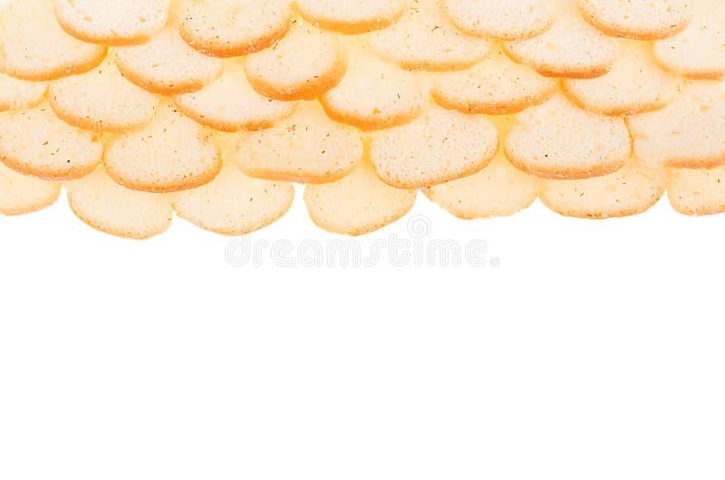 Piccoli crostini bianchi della pagnotta rubiconda come confine isolato su fondo bianco, vista superiore Fondo degli alimenti a ra immagine stock libera da diritti