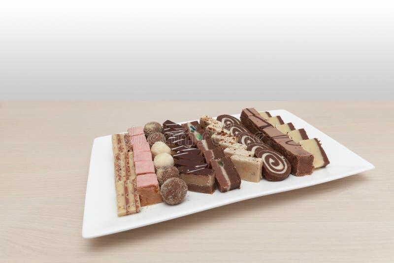 Piccoli dolci sul piatto bianco fotografie stock libere da diritti