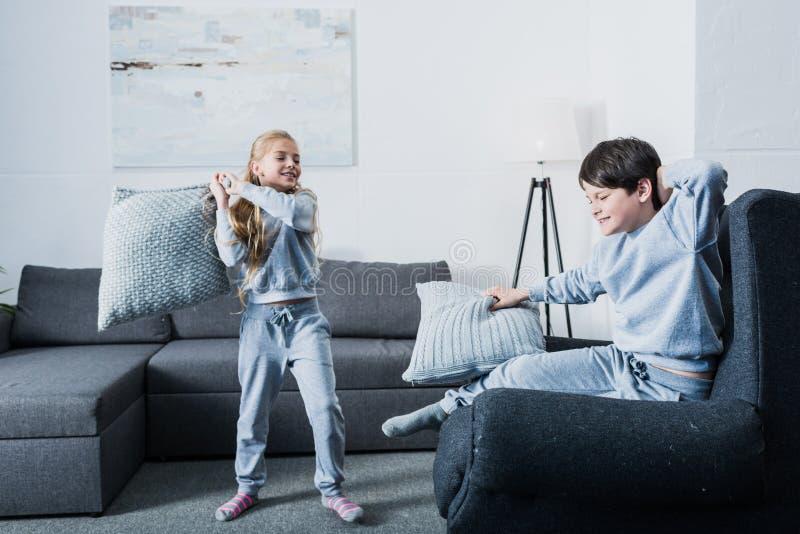 Piccoli fratelli germani in pigiami che combattono con i cuscini a casa immagine stock