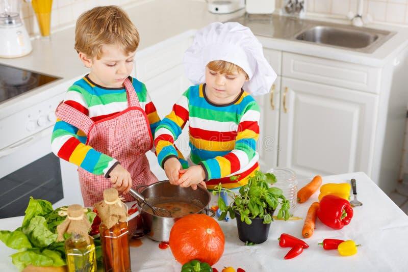 Piccoli gemelli che cucinano minestra e pasto italiani con - Bambine che cucinano ...