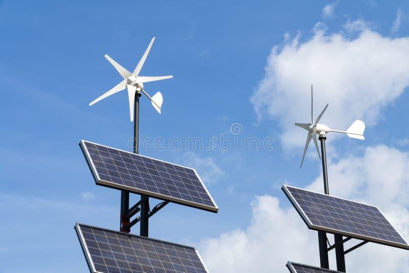Piccoli generatori eolici ed insieme del cielo blu dei agains dei pannelli solari con le nuvole bianche immagine stock libera da diritti