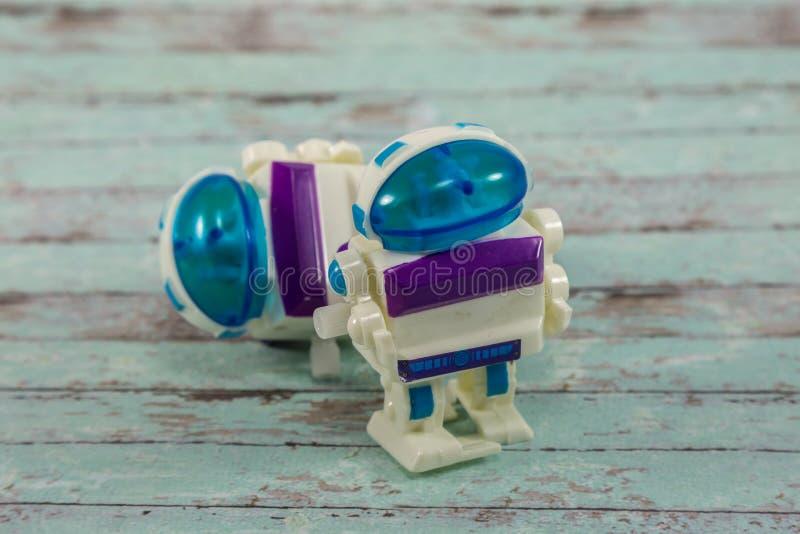 Piccoli giocattoli di plastica del robot sulla Tabella di legno bianca immagine stock libera da diritti