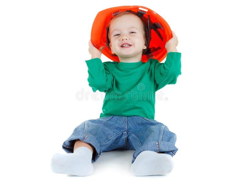 Piccoli giochi da bambini con il casco protettivo della costruzione arancio su fondo bianco fotografia stock