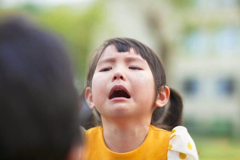 Piccoli gridare e sguardo asiatici della ragazza ai suoi genitori fotografia stock