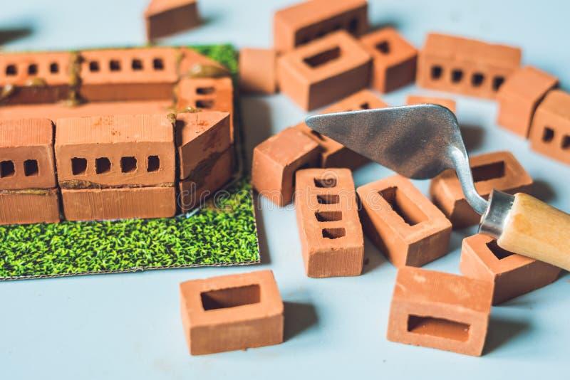 Piccoli mattoni reali dell'argilla alla tavola Presto imparando Giocattoli di sviluppo Concetto della costruzione fotografie stock