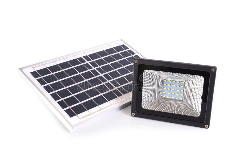 Piccoli pannello solare e riflettore per la casa su fondo bianco fotografie stock libere da diritti
