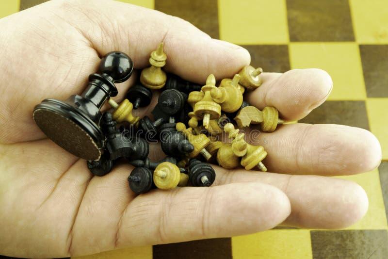 Piccoli pezzi degli scacchi di legno e un grande pegno nero nella mano di un giocatore di scacchi fotografia stock libera da diritti