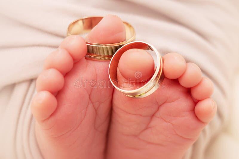 Piccoli piedi e dita del neonato con il primo piano delle fedi nuziali fotografia stock