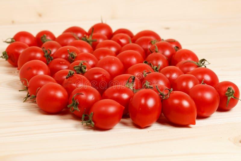Piccoli pomodori ed erbe fresche su fondo di legno immagine stock