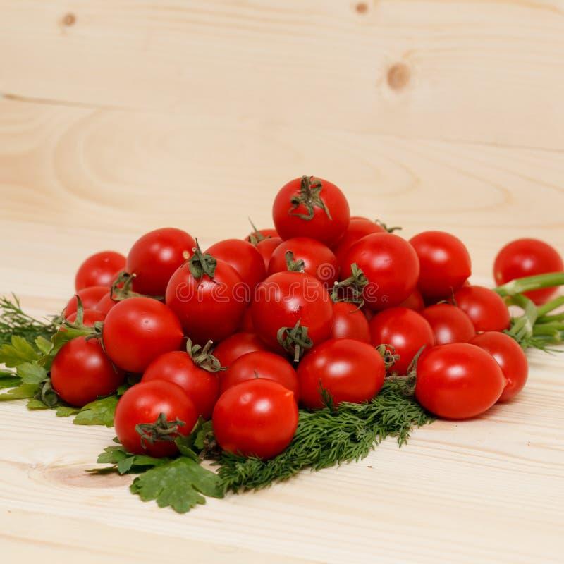 Piccoli pomodori ed erbe fresche su fondo di legno fotografie stock
