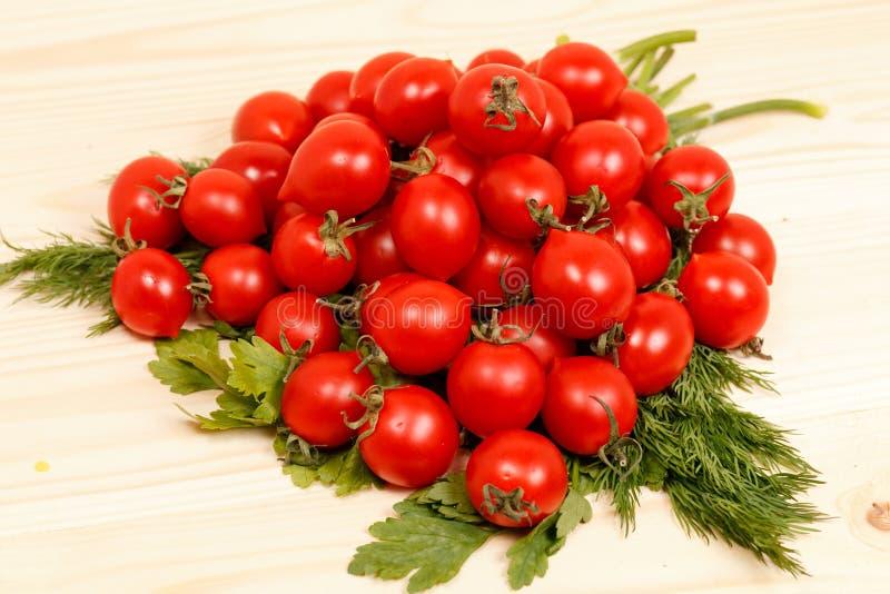 Piccoli pomodori ed erbe fresche su fondo di legno immagini stock libere da diritti