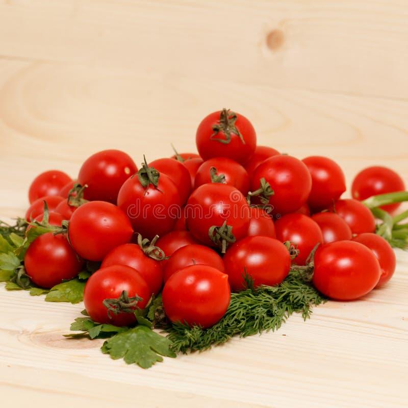 Piccoli pomodori ed erbe fresche su fondo di legno fotografie stock libere da diritti
