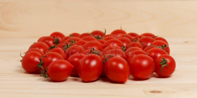 Piccoli pomodori su fondo di legno leggero fotografie stock