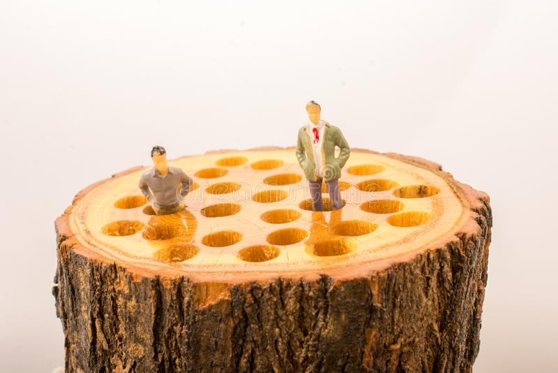Piccoli posti delle figurine degli uomini sul ceppo di legno fotografia stock