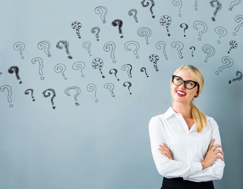 Piccoli punti interrogativi con la giovane donna immagine stock