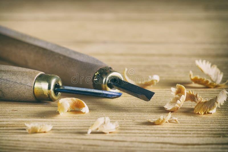 Piccoli scalpelli su un bordo di legno con i trucioli fotografia stock