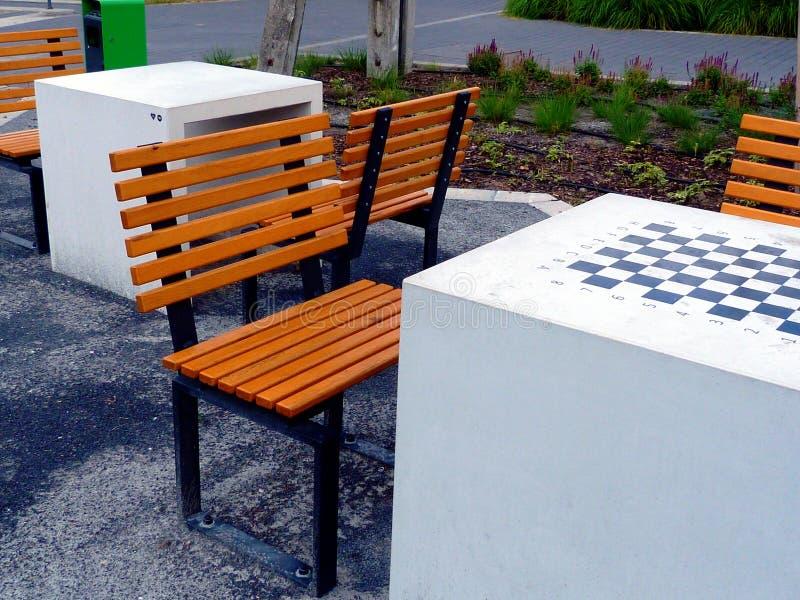 Piccoli sedili di legno gialli e neri luminosi del parco intarsio della scacchiera in tavola immagini stock