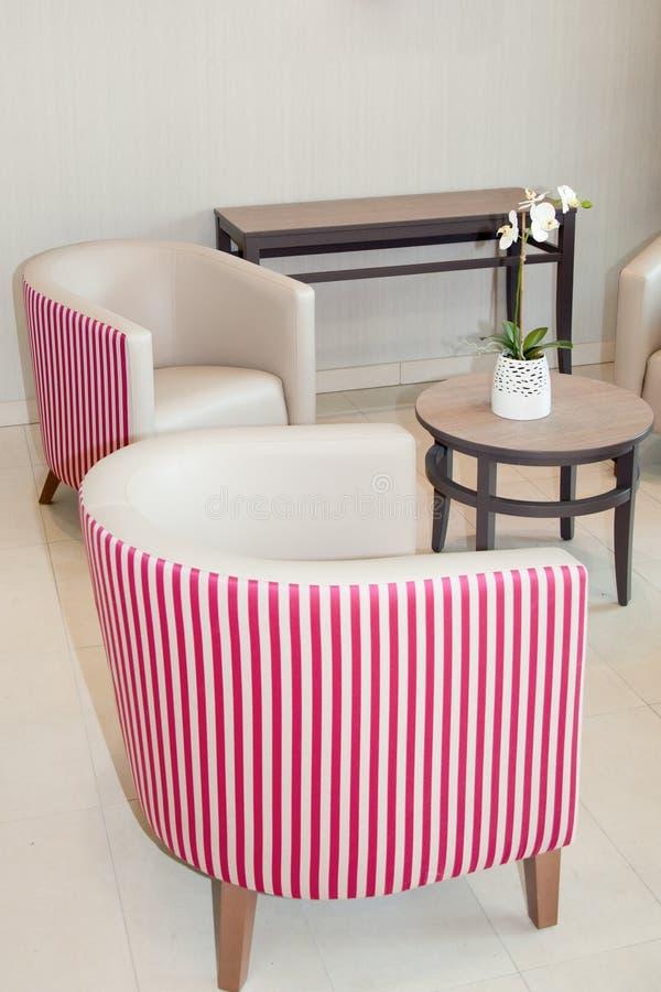 piccoli sedili a strisce bianchi e rosa nel salone immagine stock