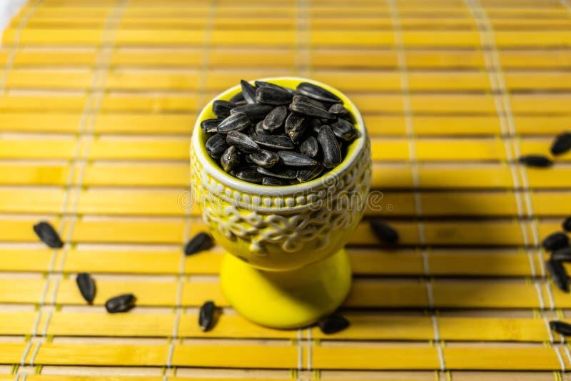 Piccoli semi di girasole neri Clicchi i semi con le bucce Una manciata in un supporto miniatura giallo su un tovagliolo di legno  immagini stock