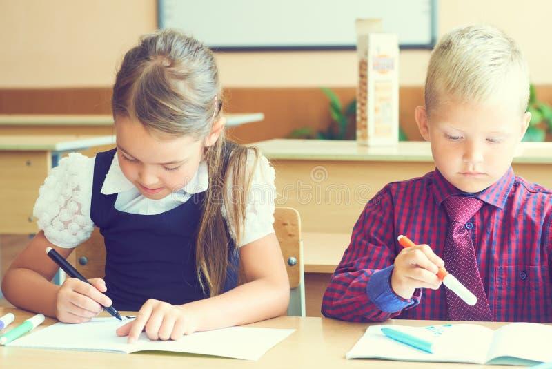 Piccoli studenti che dipingono con le penne del feltro nella classe di scuola Ritratto dei bambini nell'asilo immagine stock libera da diritti