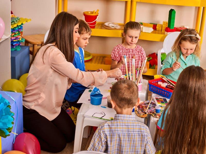 Piccoli studenti con la pittura dell'insegnante nella classe di scuola di arte fotografia stock libera da diritti