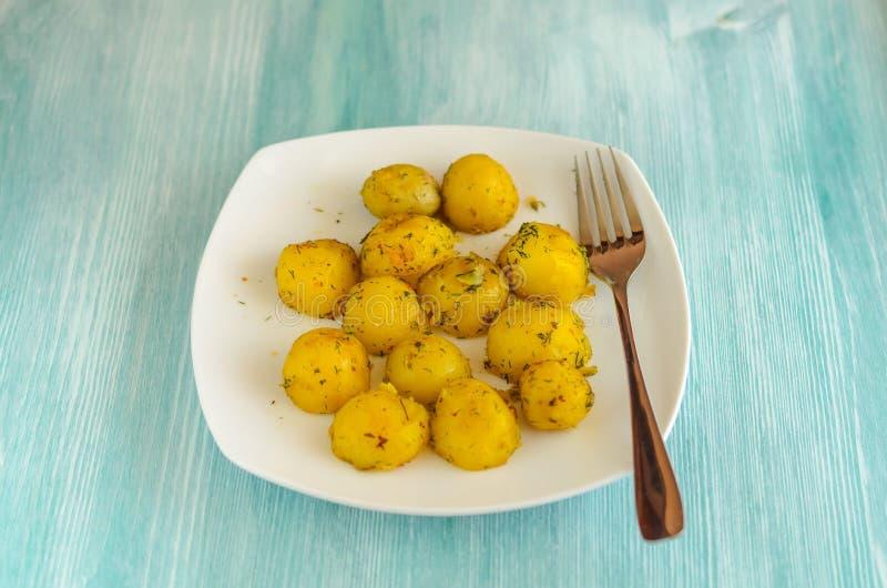 Piccoli tuberi arrostiti della patata con le spezie sul piatto bianco fotografia stock libera da diritti
