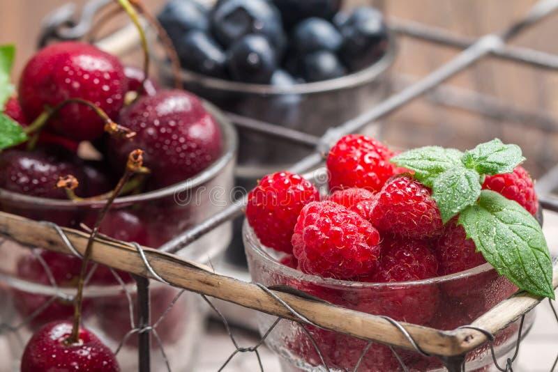 Piccoli vetri di frutta che contenente ciliegia, mirtillo e rasberry immagini stock libere da diritti