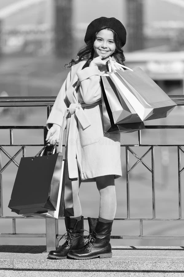 Piccolo acquisto del bambino Sacchetti della spesa alla moda del mazzo della tenuta del bambino Cappotto e berretto svegli di sig fotografia stock libera da diritti