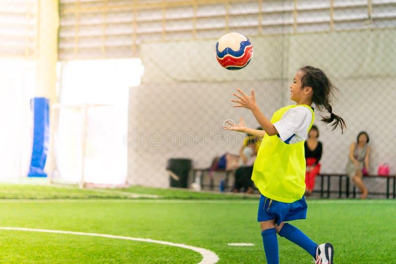 Piccolo addestramento asiatico della ragazza nel campo di calcio dell'interno immagini stock libere da diritti