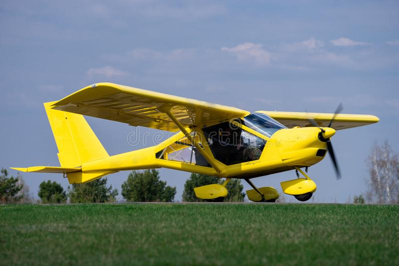 Piccolo aeroplano giallo dello statuto che aspetta su un campo verde per decollare fotografia stock libera da diritti