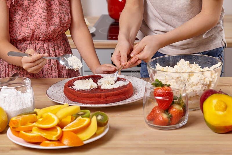 Piccolo amici sta facendo insieme un dolce ad una cucina contro una parete bianca con gli scaffali su  fotografia stock libera da diritti