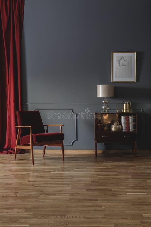 Piccolo armadietto di legno con i libri, la decorazione e la lampada disposti nel grey fotografia stock libera da diritti