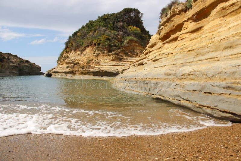 Piccolo baia con Cliff And Wave fotografie stock