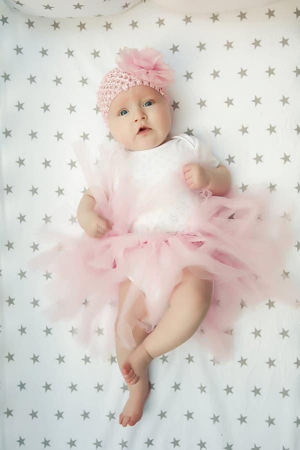 Piccolo ballerina dolce sorridente della neonata con la gonna ed il fiore rosa lanuginosi nella culla Infanzia felice Vista super immagini stock