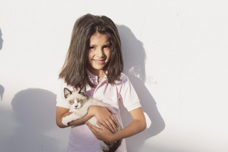 Piccolo bambini e gatto del cucciolo dell'animale domestico nell'immagine di aria aperta fotografia stock libera da diritti
