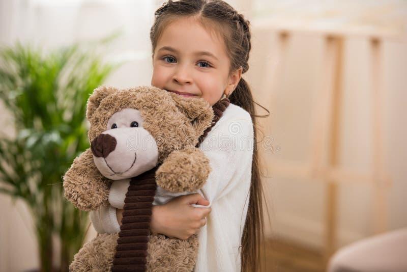 piccolo bambino adorabile che abbraccia orsacchiotto e sorridere fotografia stock