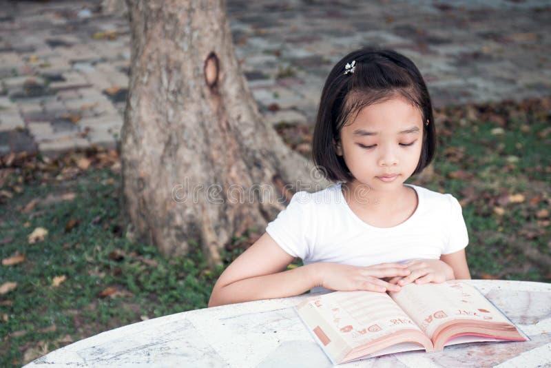 Piccolo bambino asiatico che legge un libro fotografia stock
