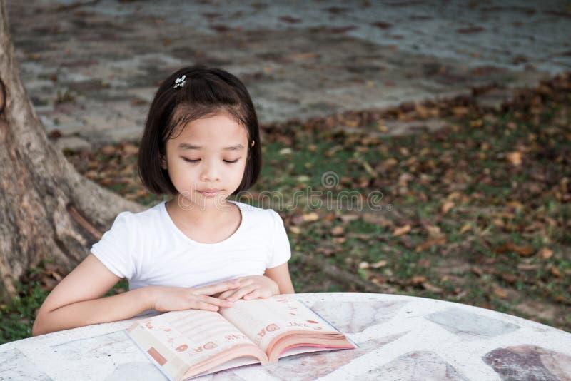 Piccolo bambino asiatico che legge un libro fotografia stock libera da diritti